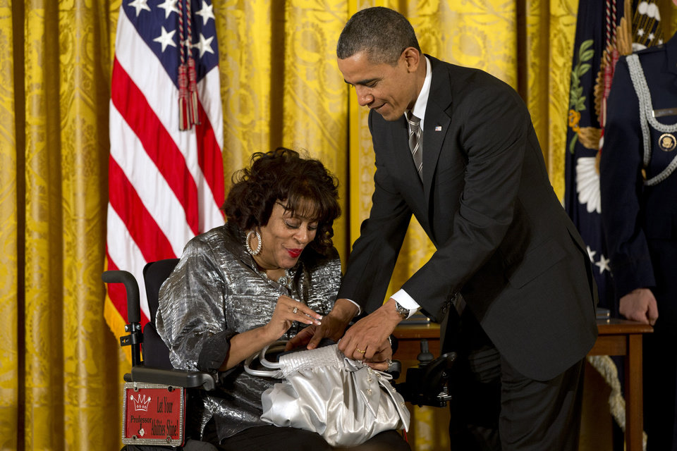President Barack Obama helps put a 2012 Citizens Medal into the purse of Janice Jackson of Baltimore, Friday, Feb. 15, 2013, during a ceremony in the East Room of the White House in Washington. Jackson is the creator and program director of Women Embracing Abilities Now, (W.E.A.N.) a nonprofit mentoring organization servicing women and young ladies with varying degrees of disabilities.  (AP Photo/Jacquelyn Martin)
