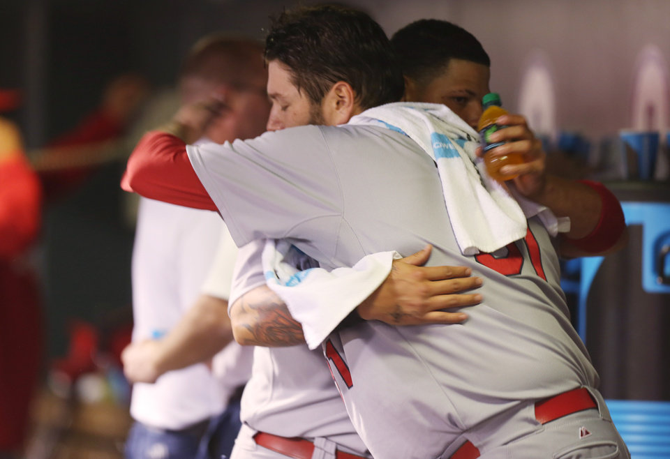 Photo - St. Louis Cardinals starting pitcher Lance Lynn, front, hugs catcher Yadier Molina after Lynn retired the Colorado Rockies in the eighth inning of the Cardinals' 8-0 victory in a baseball game in Denver on Monday, June 23, 2014. Lynn earned his eighth win of the season. (AP Photo/David Zalubowski)