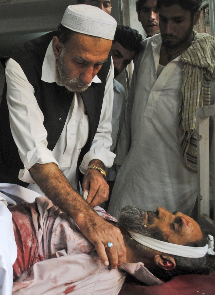 A Pakistani man checks the body of a man killed in a car bomb explosion in the Pakistani town of Darra Adam Khel in the troubled Khyber Pakhtunkhwa province, at a hospital in Peshawar, Pakistan, Saturday, Oct. 13, 2012. A powerful car bomb went off outside the offices of pro-government tribal elders in northwestern Pakistan on Saturday, killing several people, police said. (AP Photo/Mohammad Sajjad)