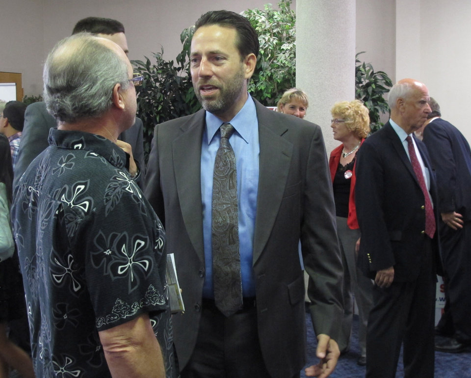 Photo - Republican U.S. Senate hopeful Joe Miller speaks to a man during