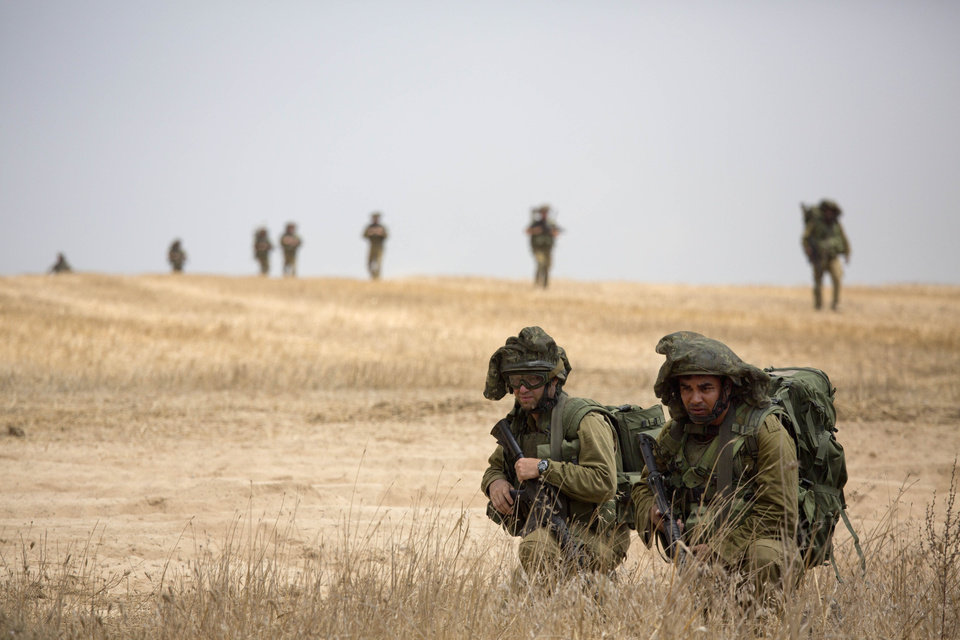 Photo - CORRECTS BYLINE - Israeli soldiers march during a drill near the Israel and Gaza border, Tuesday, July 22, 2014. Israeli airstrikes pummeled a wide range of locations in the Gaza Strip on Tuesday as the U.N. chief and the U.S. secretary of state began an intensive effort to end more than two weeks of fighting that has killed hundreds of Palestinians and dozens of Israelis.(AP Photo/Dusan Vranic)