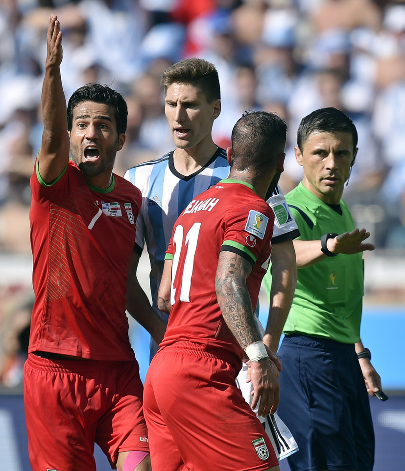 Photo - Iran's Masoud Shojaei and Ashkan Dejagah (21) argue with referee Milorad Mazic from Serbia during the group F World Cup soccer match between Argentina and Iran at the Mineirao Stadium in Belo Horizonte, Brazil, Saturday, June 21, 2014. (AP Photo/Martin Meissner)