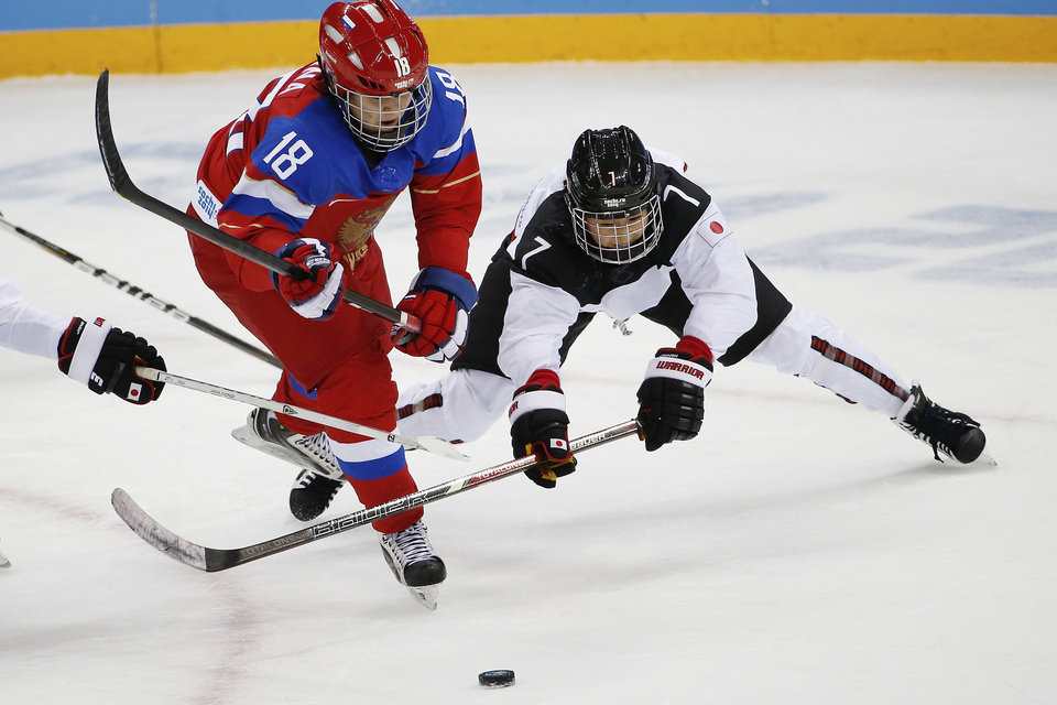 Photo - Olga Sosina of Russia and Mika Hori of Japan battle for control of the puck during the 2014 Winter Olympics women's ice hockey game at Shayba Arena Sunday, Feb. 16, 2014, in Sochi, Russia. (AP Photo/Petr David Josek)