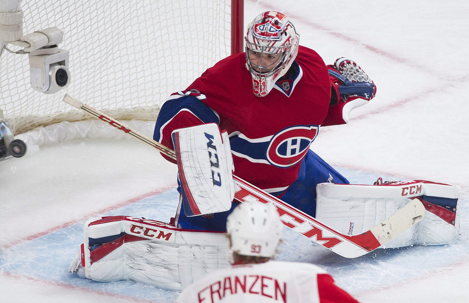 Photo - Montreal Canadiens goaltender Carey Price makes a save against Detroit Red Wings' Johan Franzen during the second period of an NHL hockey game in Montreal, Saturday, April 5, 2014. (AP Photo/The Canadian Press, Graham Hughes)