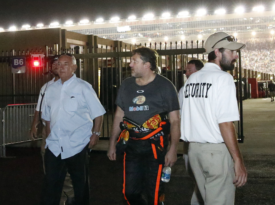 Photo - Sprint Cup Series driver Tony Stewart (14) walks to his motorhome after hitting the wall and retiring from a  NASCAR Sprint Cup auto race at Atlanta Motor Speedway Sunday, Aug. 31, 2014, in Hampton, Ga..  (AP Photo/Brynn Anderson)