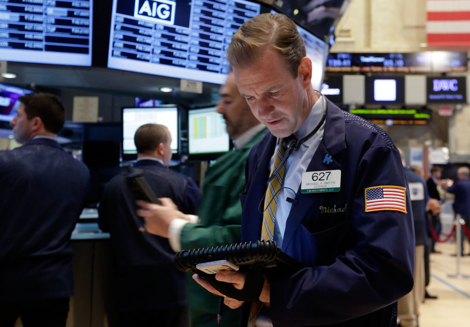 Photo - Trader Michael Smyth works on the floor of the New York Stock Exchange Monday, April 28, 2014. Stocks are mostly higher in early trading as traders hope for another blockbuster merger in the health-care industry. (AP Photo/Richard Drew)