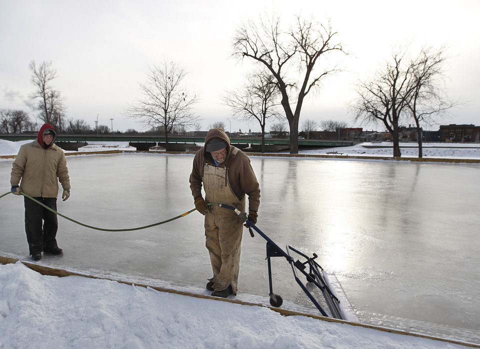 Photo - Zac Hornung, left, and Harold Runkle, right, with the Cedar Falls Parks Department put another layer of ice on the Gateway park ice rink, Tuesday, Jan. 21, 2014, in Cedar Falls, Iowa. (AP Photo/Waterloo Courier, Matthew Putney)