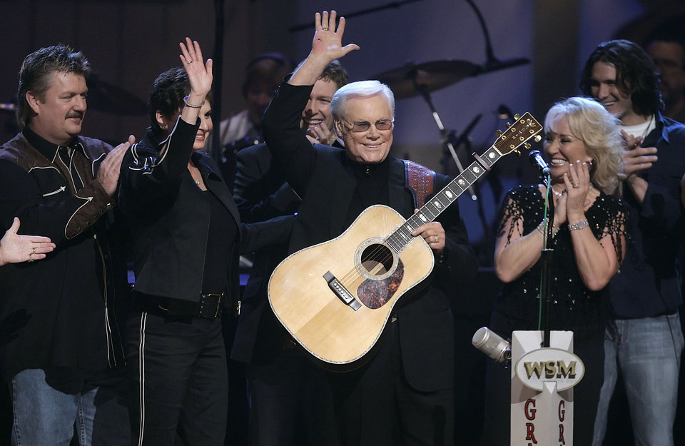 Photo - FILE - In this Sept. 12, 2006 file photo, Country music legend George Jones waves to the crowd during his 75th birthday celebration at the Grand Ole Opry House in Nashville, Tenn., on Tuesday, Sept. 12, 2006. From left are Joe Diffie; Jones' wife, Nancy; Craig Morgan; Jones; Tanya Tucker; and Joe Nichols.   Jones, the peerless, hard-living country singer who recorded dozens of hits about good times and regrets and peaked with the heartbreaking classic