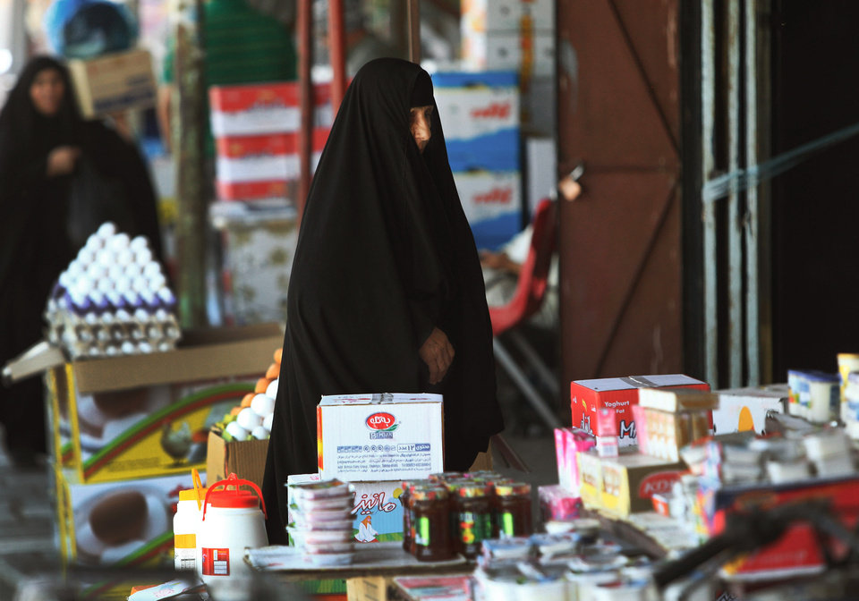 Photo - Iraqi women at a market in Basra, Iraq's second-largest city, 340 miles (550 kilometers) southeast of Baghdad, Iraq, Thursday, June 19, 2014. Since June 6, Sunni fighters led by an al-Qaida breakaway group, the Islamic State of Iraq and the Levant, have swept through Iraq, seizing the second largest city, Mosul and Saddam Hussein's hometown of Tikrit as thousands of Iraqi soldiers melted away. The insurgents are now pressing to Baghdad. (AP Photo/ Nabil Al-Jurani)