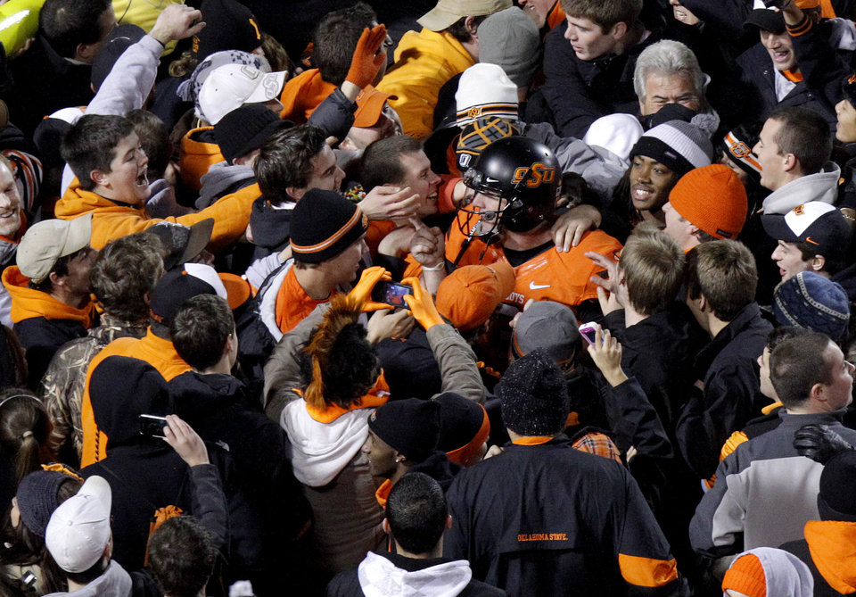 Photo - Oklahoma State's Brandon Weeden (3) celebrates with fans following the Bedlam college football game between the Oklahoma State University Cowboys (OSU) and the University of Oklahoma Sooners (OU) at Boone Pickens Stadium in Stillwater, Okla., Saturday, Dec. 3, 2011. Photo by Bryan Terry, The Oklahoman
