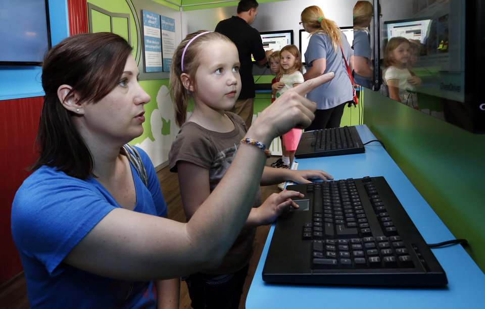 Photo -  Emily Hayes and her daughter Caton, 6, look at devices in the Digital Bookmobile as it stops in Norman as part of a national tour. PHOTO BY STEVE SISNEY, THE OKLAHOMAN   STEVE SISNEY -