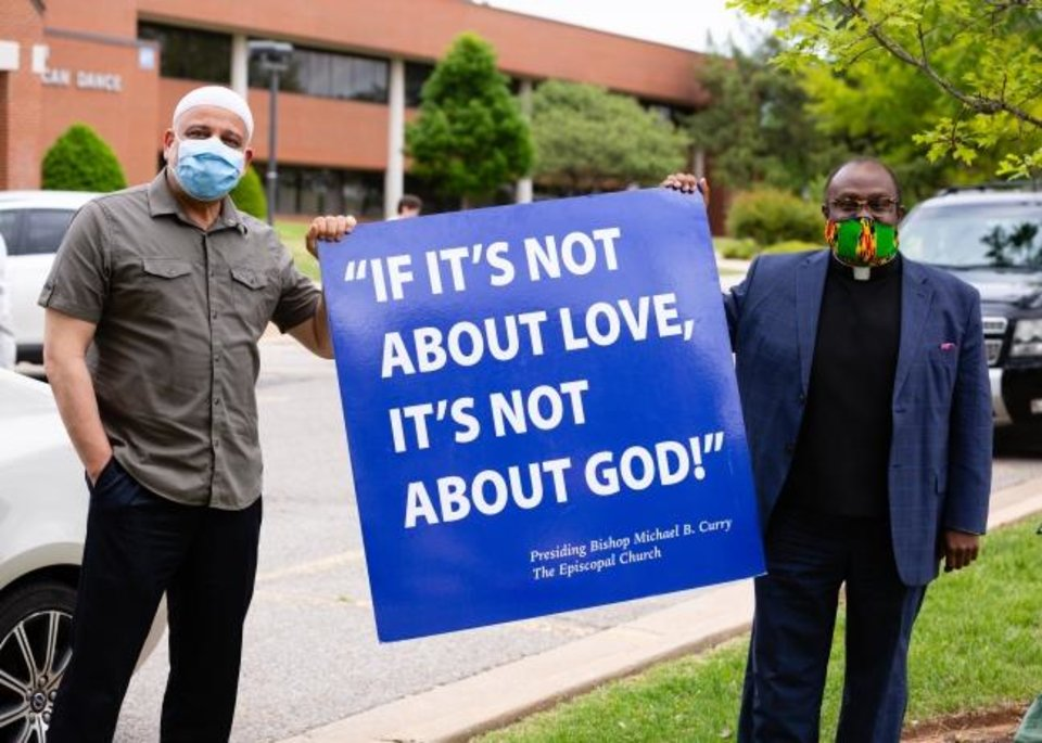 Photo -  Imad Enchassi, Oklahoma City University Islamic studies professor and Islamic Society of Greater Oklahoma City senior imam, and the   Rev. Joseph Alsay, rector of St. Augustine of Canterbury Episcopal church, holds up a sign outside OCU as part of the