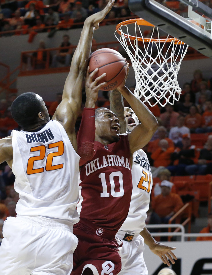 Photo - Oklahoma guard Jordan Woodard(10) shoots between Oklahoma State wing Markel Brown (22) and post Kamari Murphy (21) in the first half of an NCAA college basketball game in Stillwater, Okla., Saturday, Feb. 15, 2014. (AP Photo/Sue Ogrocki)