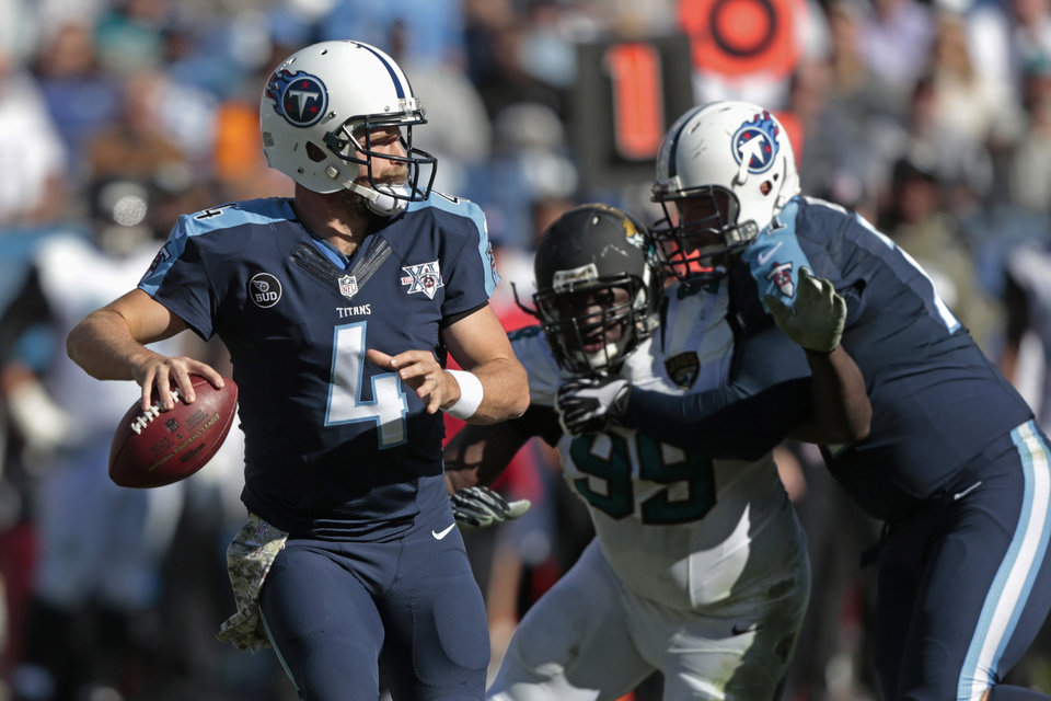 Photo - Tennessee Titans quarterback Ryan Fitzpatrick (4) passes as Titans tackle Michael Roos, right, blocks Jacksonville Jaguars defensive tackle Sen'Derrick Marks (99) in the first half of an NFL football game on Sunday, Nov. 10, 2013, in Nashville, Tenn. (AP Photo/Wade Payne)