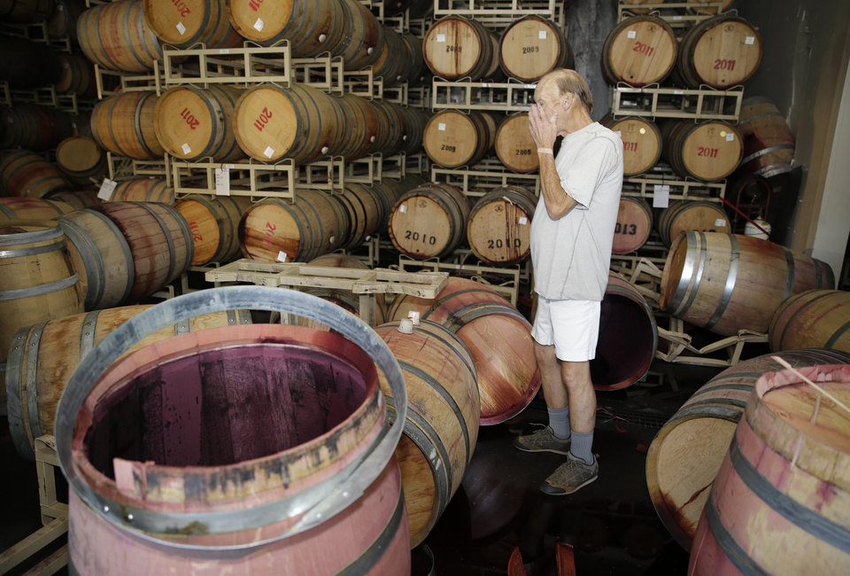 Photo - File - This Aug. 24, 2014 file photo shows winemaker Tom Montgomery standing in wine as he reacts to seeing damage following an earthquake at the B.R. Cohn Winery barrel storage facility in Napa, Calif. Napa Valley's seismically reinforced winery buildings generally held up to the largest earthquake to hit Northern California in a quarter-century, but the precious wine piled inside often did not. (AP Photo/Eric Risberg, file)