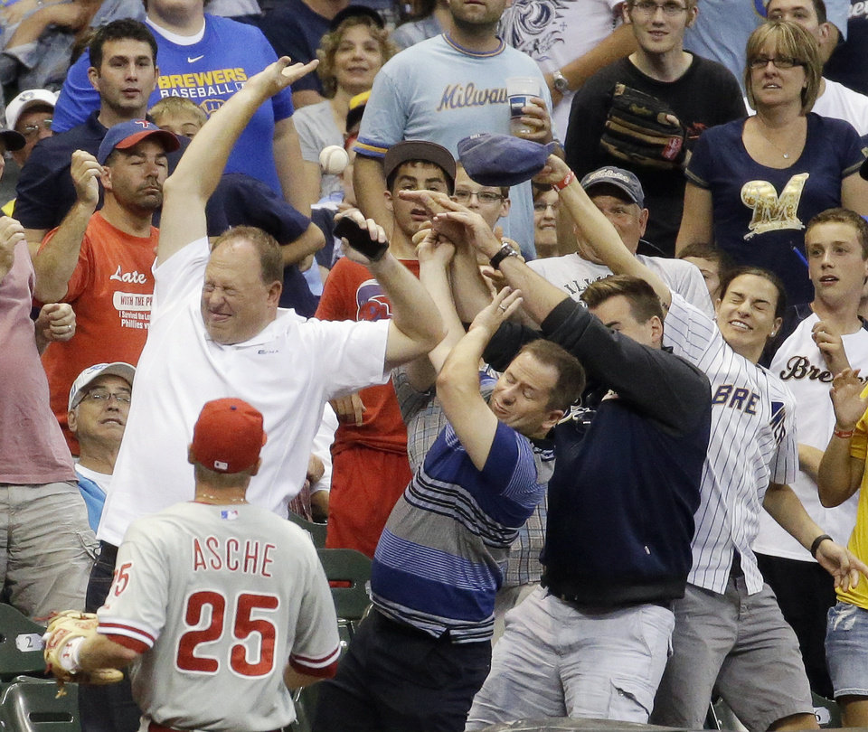 Photo - Philadelphia Phillies' Cody Asche watches as fans go after a foul ball off the bat of Milwaukee Brewers' Logan Schafer during the fourth inning of a baseball game Tuesday, July 8, 2014, in Milwaukee. (AP Photo/Morry Gash)