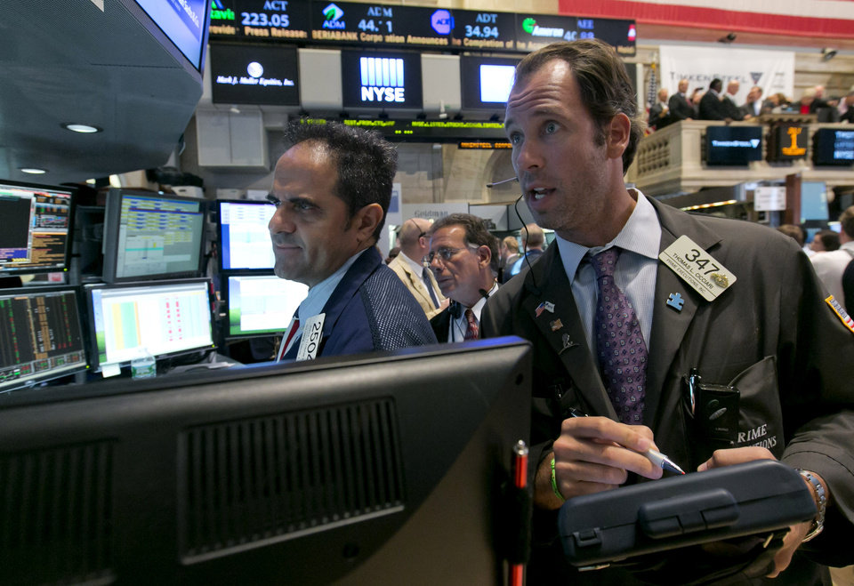 Photo - Trader Thomas Cicciari, right, and specialist Jorge Fernanadez work on the floor of the New York Stock Exchange Tuesday, July 1, 2014. The stock market rose in early trading after a report showed that manufacturing in the US and China expanded in June, boosting the outlook for global growth. (AP Photo/Richard Drew)