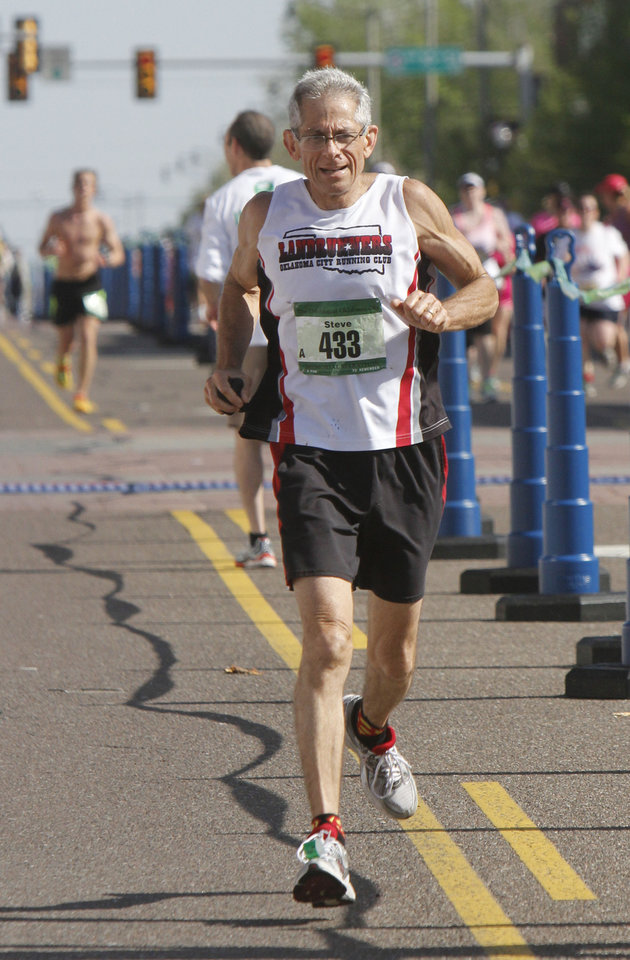 Photo - 61-year-old Steve Spielman finishes the Oklahoma City Memorial Marathon in Oklahoma City, Sunday, April 28, 2013,  By Paul Hellstern, The Oklahoman