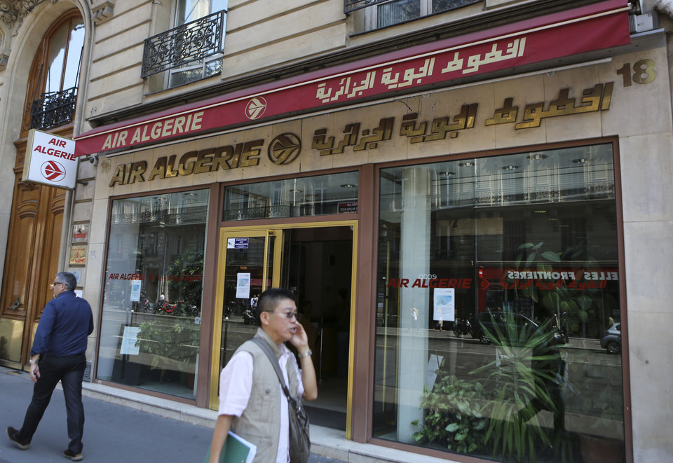 Photo - Passersby walk past the Air Algerie company office, on the Opera Avenue in Paris Thursday July 24, 2014. A flight operated by Air Algerie has disappeared from radar while traveling from Burkina Faso in West Africa to Algiers. Authorities say it was carrying over 100 passengers and crew when air navigation services lost track of the Swiftair plane 50 minutes after takeoff earlier this morning. (AP Photo/Remy de la Mauviniere)