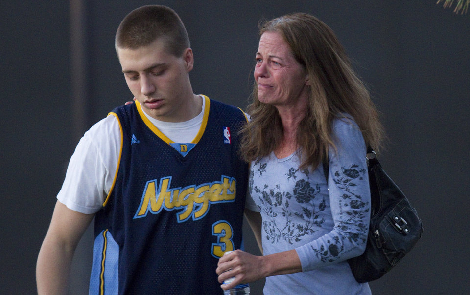 Photo - Eyewitness Jacob Stevens, 18, hugs his mother Tammi Stevens after being interview by police outside Gateway High School where witnesses were brought for questioning Friday, July 20, 2012 in Aurora, Colo.   A gunman wearing a gas mask set off an unknown gas and fired into the crowded movie theater killing 12 people and injuring at least 50 others, authorities said. (AP Photo/Barry Gutierrez) ORG XMIT: COBG104