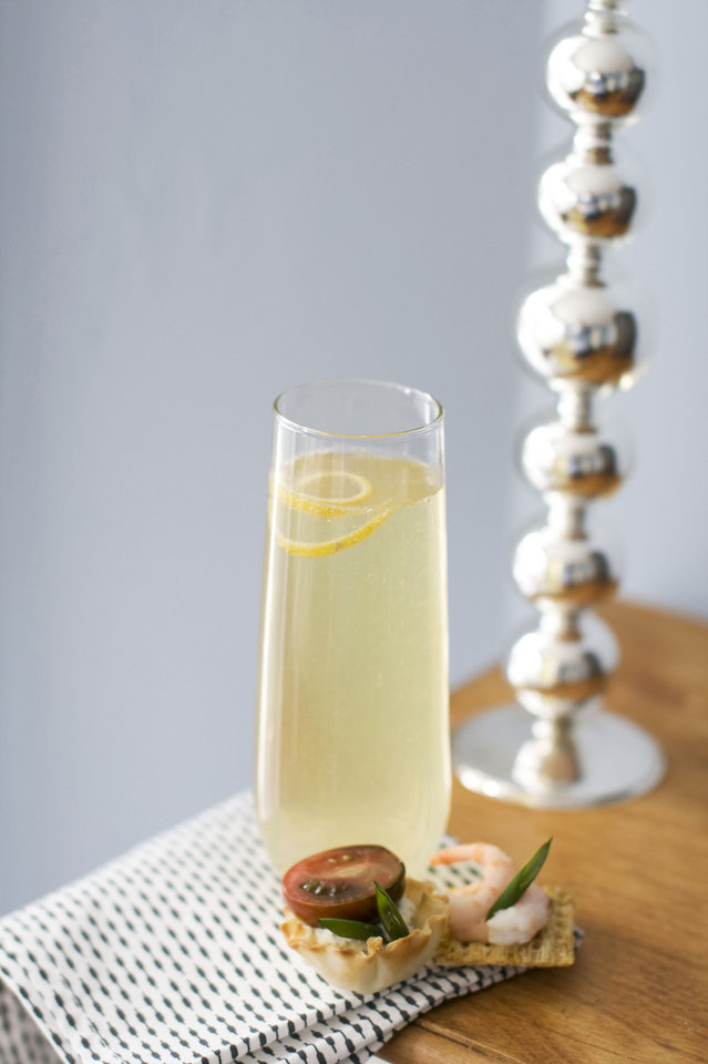 In this image taken on Jan. 28, 2013, a glass of citrus bubbly with a small curl of lemon on top is shown next to canapes on a table in Concord, N.H. (AP Photo/Matthew Mead) ORG XMIT: NYLS861