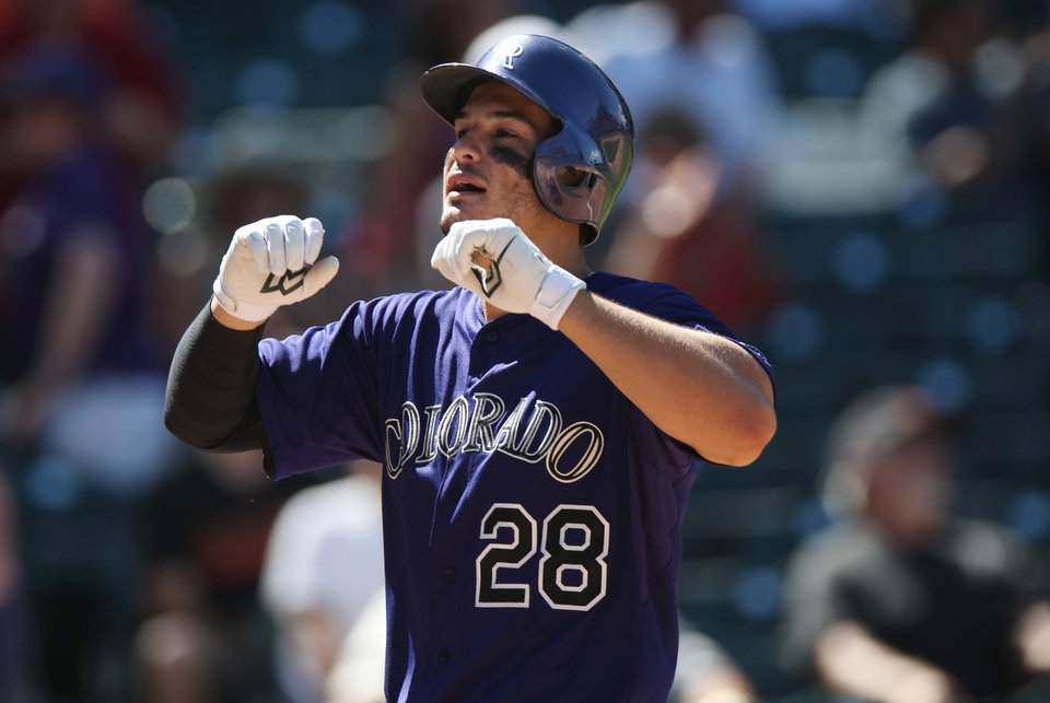 Photo - Colorado Rockies' Nolan Arenado celebrates his three-run home run as he crosses home plate against the San Francisco Giants in the fifth inning of the Rockies' 9-2 victory in a baseball game in Denver on Wednesday, Sept. 3, 2014. (AP Photo/David Zalubowski)