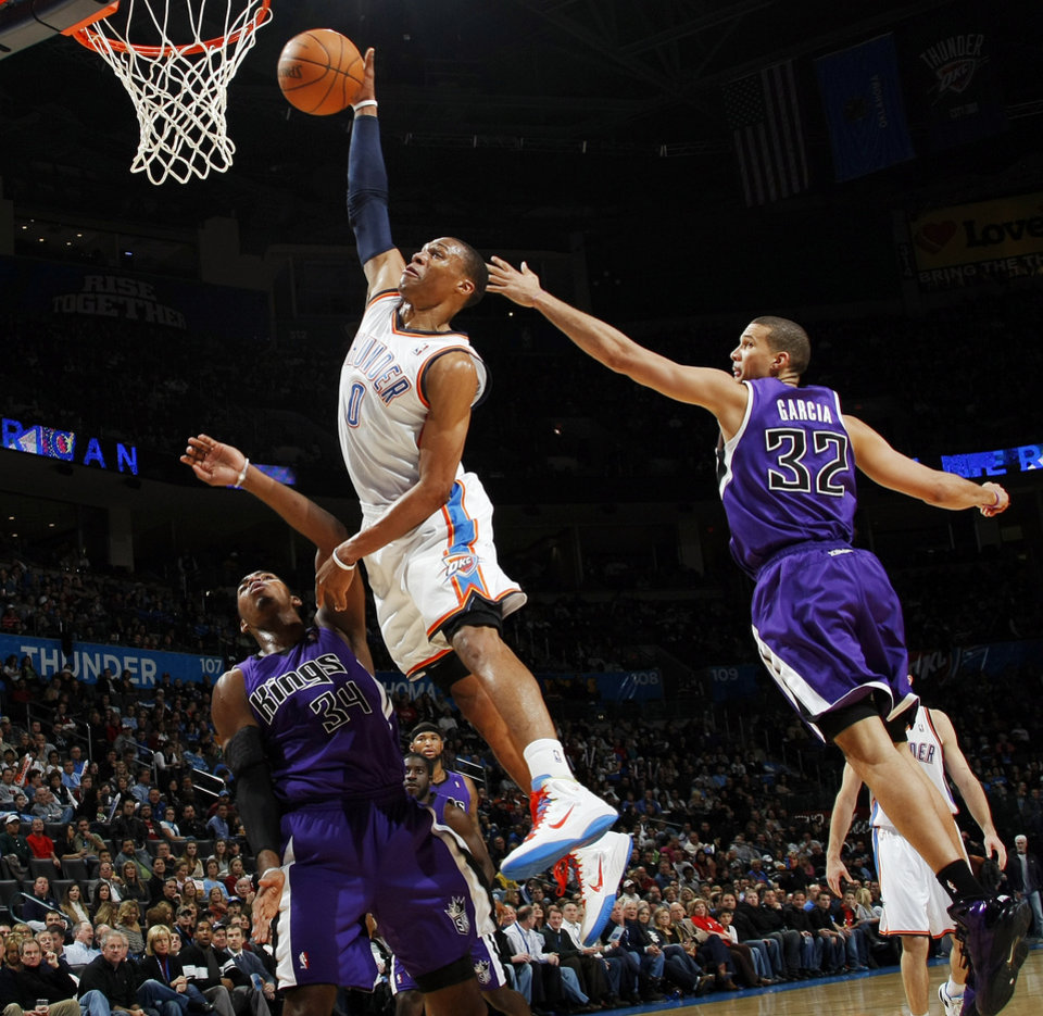 Oklahoma City's Russell Westbrook (0) tries to dunk the ball between Jason Thompson (34) and Francisco Garcia (32) of Sacramento during the NBA basketball game between the Sacramento Kings and the Oklahoma City Thunder at the Oklahoma City Arena in Oklahoma City, Friday, December 17, 2010. Photo by Nate Billings, The Oklahoman