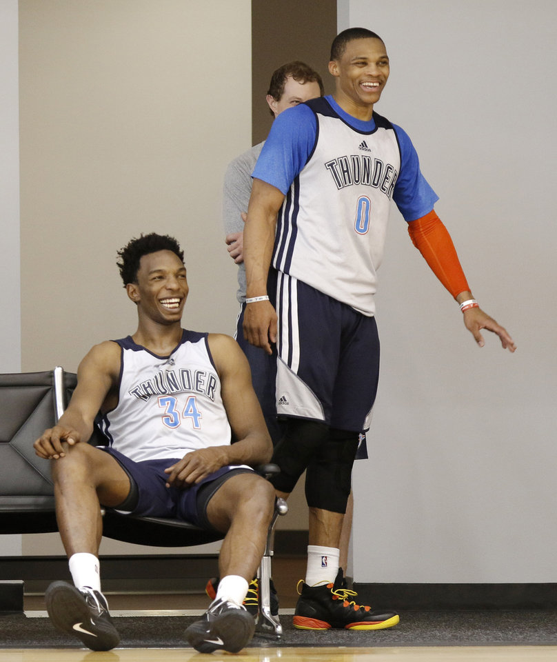 Photo - Hasheem Thabeet, seated, and Russell Westbrook laugh at the antics of teammates during the Thunder practice Wednesday, February 19, 2014. PHOTO BY DOUG HOKE, The Oklahoman