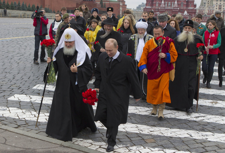 Russian President Vladimir Putin, center, walks with flowers across Red Square to place them at the statue of Minin and Pozharsky, the leaders of a struggle against foreign invaders in 1612, to mark the National Unity Day, Sunday, Nov. 4, 2012. The new holiday was created in 2005 to replace the traditional Nov. 7 celebration of the 1917 Bolshevik rise to power. The Kremlin has tried to give it historical significance by tying it to the 1612 expulsion of Polish and Cossack troops who briefly seized Moscow at a time of political disarray. But it has been seized upon by extreme nationalists. Putin is followed by various religious leaders of different confessions.(AP Photo/ Misha Japaridze)