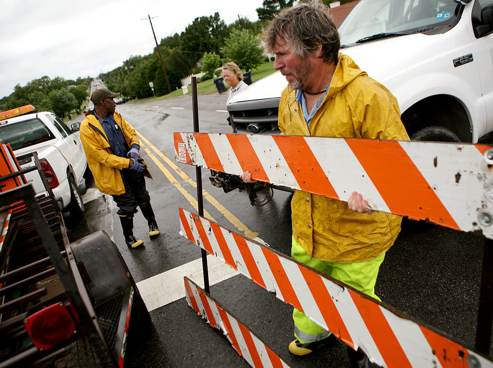 Photo - City employee Gil Barnes, puts up a roadblock at Hefner road and Macarthur as water spills over the dam south of Hefner between Macarthur and Rockwell in Oklahoma City on Monday, June 14, 2010. Photo by John Clanton, The Oklahoman