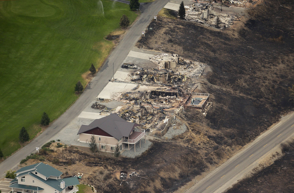 Photo - This aerial photo shows homes destroyed by wildfires near Pateros, Wash. on Thursday, July 24, 2014. Fire spokesman Pete Buist says the biggest wildfire in the state's history remains at 52 percent contained on Thursday. However, the weather forecast calls for hot and dry conditions to return over the next few days. (AP Photo)