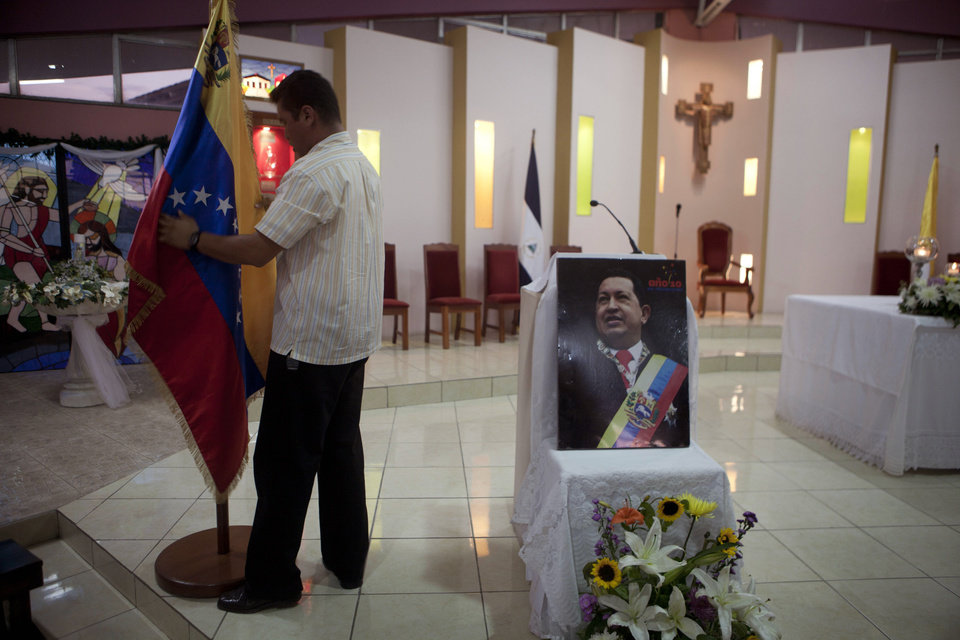 Photo - A man prepares a Venezuelan flag next to an image of Venezuela's President Hugo Chavez before a mass in support of him in Managua, Nicaragua, Wednesday Dec. 12, 2012. Venezuela's Information Minister Ernesto Villegas expressed hope about Chavez returning home for his Jan. 10 swearing-in for a new six-year term after his cancer surgery in Cuba, but said in a written message on a government website that if Chavez doesn't make it,
