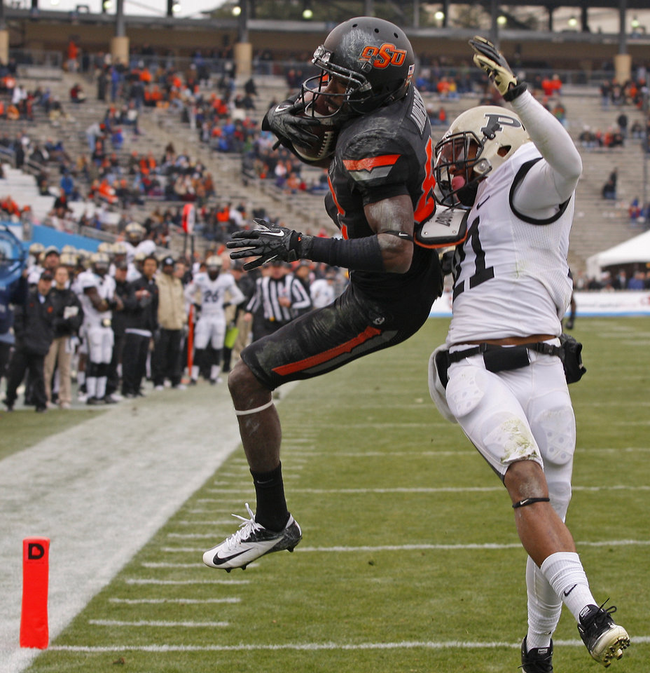 Photo - Oklahoma State's Isaiah Anderson (82) catches a touchdown in front of Purdue's Ricardo Allen (21) during the Heart of Dallas Bowl football game between Oklahoma State University and Purdue University at the Cotton Bowl in Dallas, Tuesday, Jan. 1, 2013. Oklahoma State won 58-14. Photo by Bryan Terry, The Oklahoman