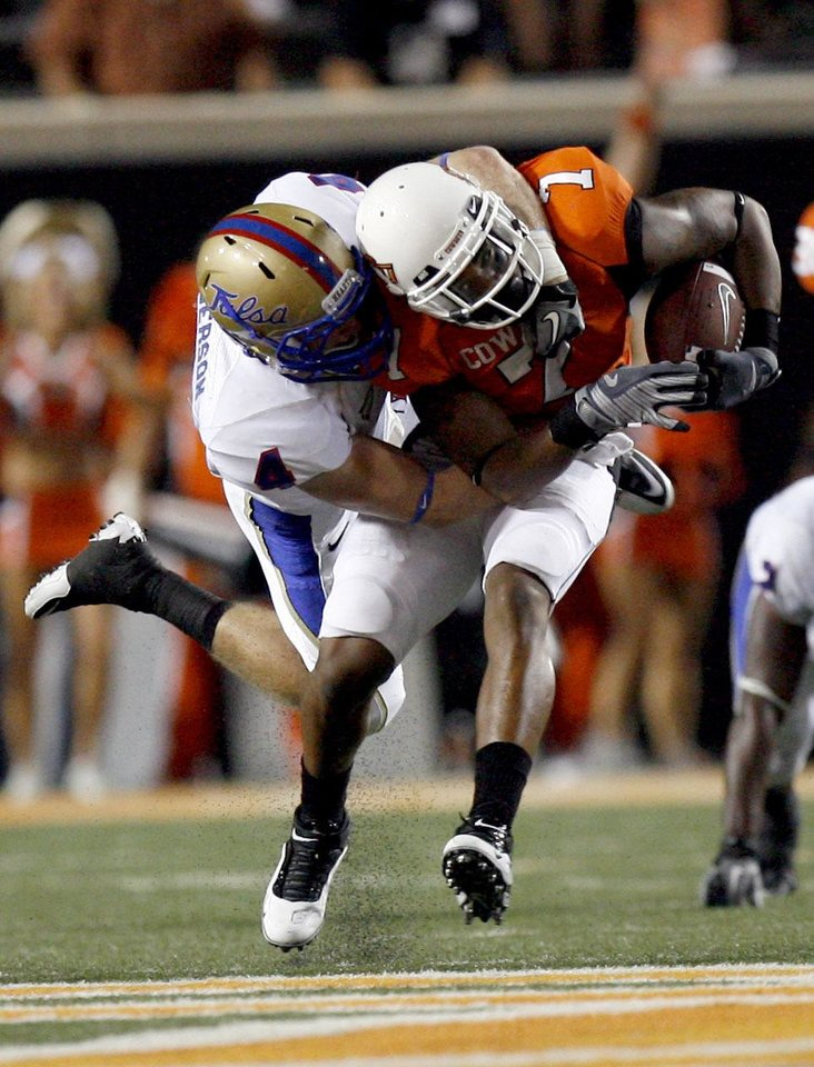 Photo - Oklahoma State wide receiver Michael Harrison (7) is tackled by Tulsa's James Roberson (4) during the college football game between the University of Tulsa (TU) and Oklahoma State University (OSU) at Boone Pickens Stadium in Stillwater, Oklahoma, Saturday, September 18, 2010. Photo by Sarah Phipps, The Oklahoman