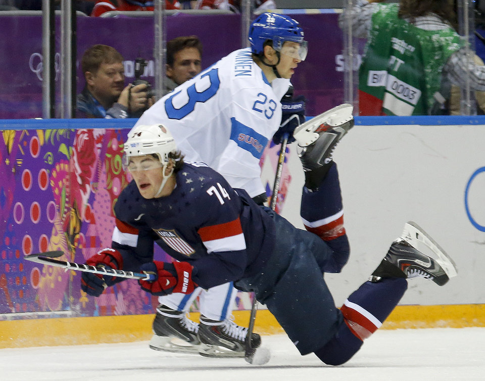 Photo - USA forward T.J. Oshie is tripped by Finland forward Sakari Salminen during the first period of the men's bronze medal ice hockey game at the 2014 Winter Olympics, Saturday, Feb. 22, 2014, in Sochi, Russia. (AP Photo/Mark Humphrey)
