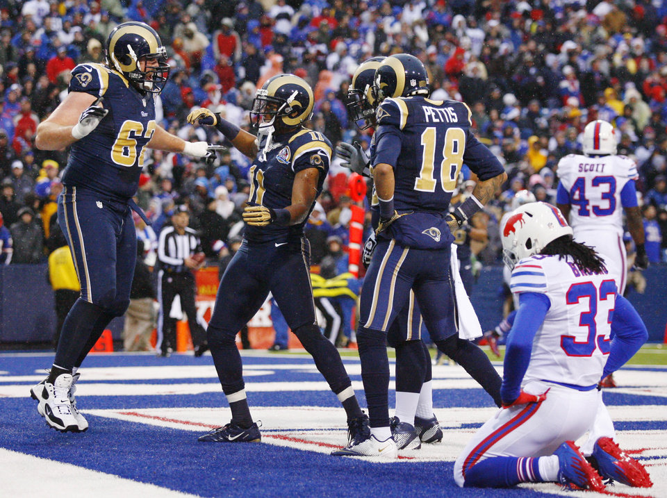 Photo - St. Louis Rams wide receiver Brandon Gibson (11) celebrates with teammates including guard Harvey Dahl (62) and wide receiver Austin Pettis (18) after catching a touchdown pass from quarterback Sam Bradford, not pictured, as Buffalo Bills cornerback Ron Brooks (33) reacts during the second half of an NFL football game, Sunday, Dec. 9, 2012, in Orchard Park, N.Y. The Rams won 15-12. (AP Photo/Bill Wippert)