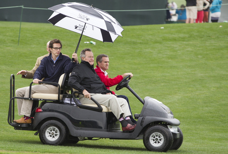 Photo - Former President George H.W. Bush rides out onto the 18th green during the final round of the Houston Open golf tournament, Sunday, April 6, 2014, in Humble, Texas. (AP Photo/Patric Schneider)