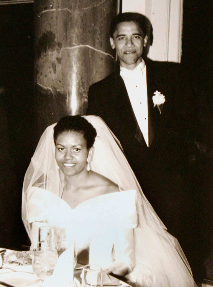 Photo - FILE-  This Oct. 18, 1992 file photo released by Obama for America shows President Barack Obama and first lady Michelle Obama on their wedding day in Chicago.  Obama's long-sleeve, portrait-collar wedding dress was one of her few fashion decisions that didn't move the needle. That was back in 1992, though.  Her one-shoulder, white inaugural gown by Jason Wu, however, turned into a bona fide bridal-gown sensation, says Miller. It came at the right time, as designers continued to move away from all strapless all the time, she observes, and Obama wore it with the right happy, confident attitude that brides strive for.    (AP Photo/Obama for America, file)