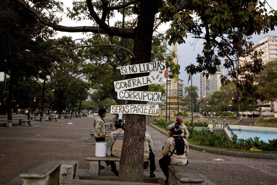 Photo - Bolivarian National Police officers sit under the shade of a tree, with placards that read in Spanish;