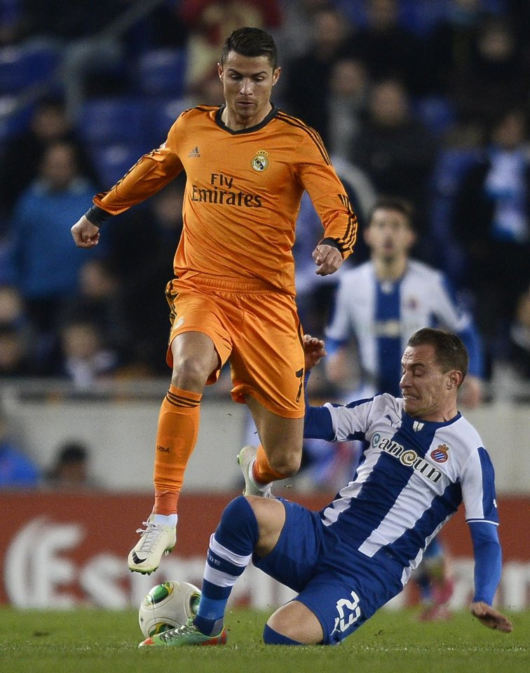 Photo - Real Madrid's Cristiano Ronaldo, from Portugal, duels for the ball against Espanyol's Abraham Gonzalez, right, during a Copa del Rey soccer match at Cornella-El Prat stadium in Cornella Llobregat , Spain, Tuesday, Jan. 21, 2014. (AP Photo/Manu Fernandez)