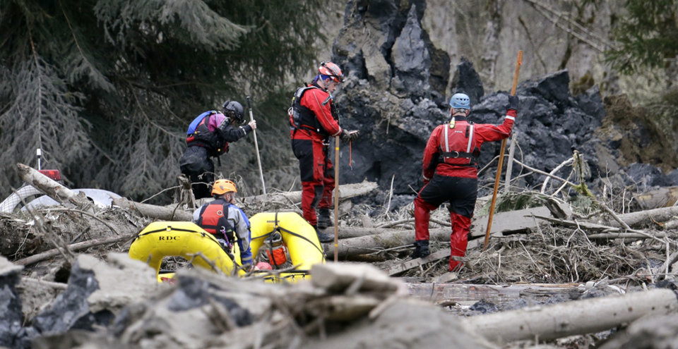 Photo - Searchers in boats and on foot look through debris following a deadly mudslide Tuesday, March 25, 2014, in Oso, Wash. At least 14 people were killed in the 1-square-mile slide that hit in a rural area about 55 miles northeast of Seattle on Saturday. Several people also were critically injured, and homes were destroyed. (AP Photo/Elaine Thompson)