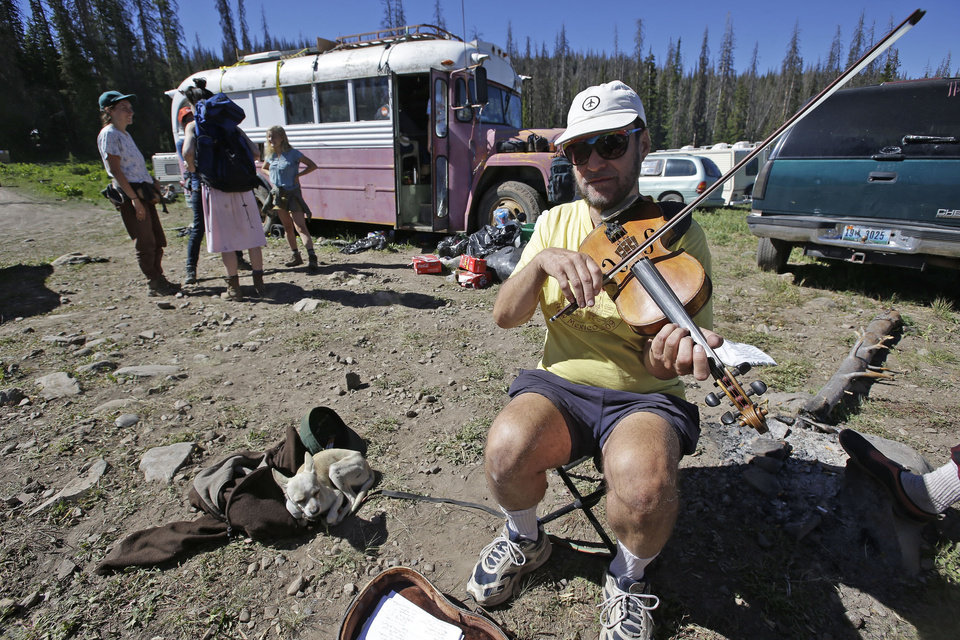 Photo - A person who identified himself as Henry the Fiddler, from Denver, performs at the beginning of the trail leading to the Rainbow Family campsites Tuesday, July 1, 2014, in the Uinta National Forest, Utah. About 4,000 members of a counterculture group known as the Rainbow Family have poured into the woods about 60 miles east of Salt Lake City for an annual festival that culminates in a four-day celebration beginning Tuesday. (AP Photo/Rick Bowmer)