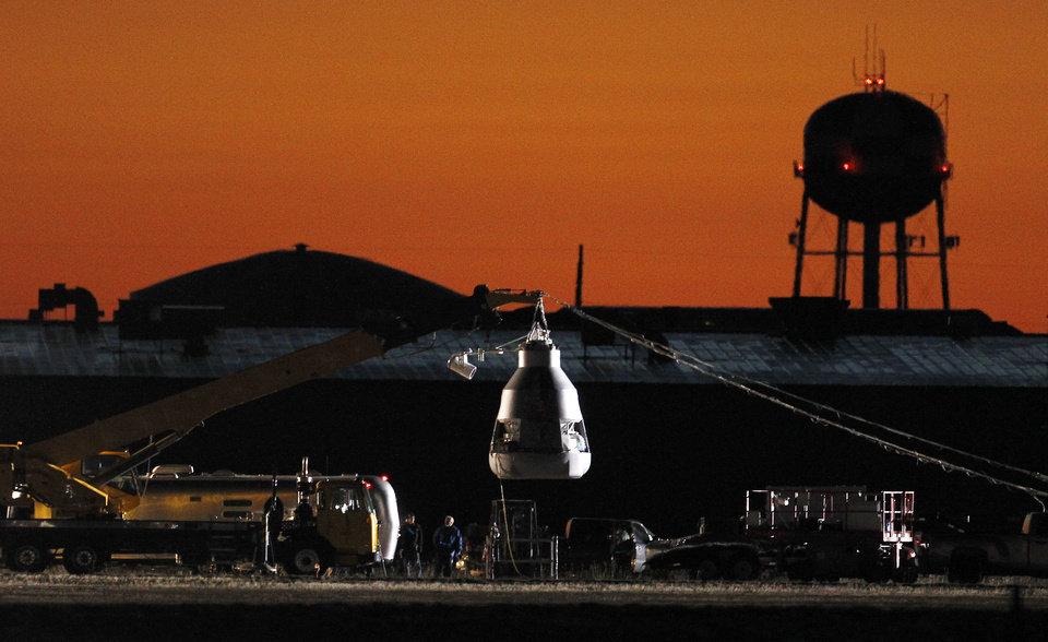 Photo -   As the sun rises, workers prepare at the launch site, ahead of an attempt by Felix Baumgartner to break the speed of sound with his own body by jumping from a space capsule lifted by a helium balloon, Sunday, Oct. 14, 2012, in Roswell, N.M. Baumgartner plans to jump from an altitude of 120,000 feet, an altitude chosen to enable him to achieve Mach 1 in free fall, which would deliver scientific data to the aerospace community about human survival from high altitudes.(AP Photo/Ross D. Franklin)