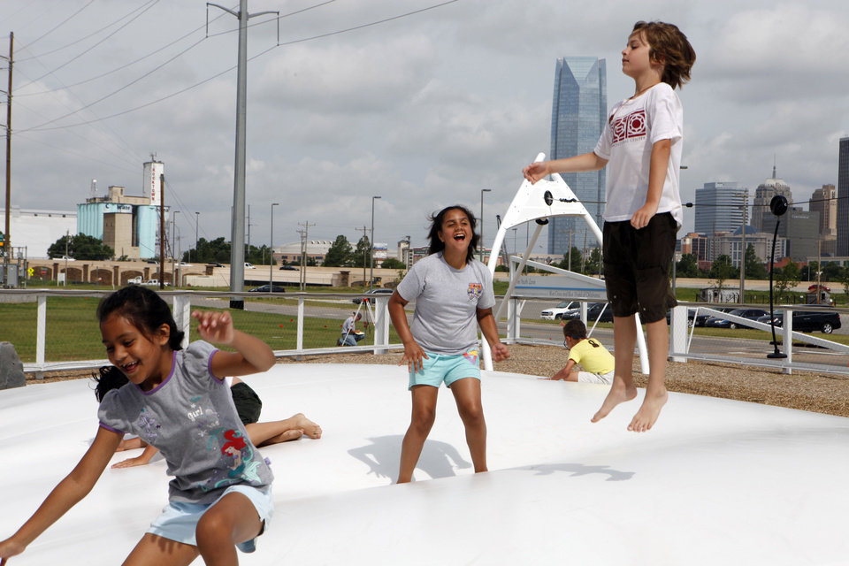 Photo - Children play on a cloud bounce during a camp at the Oklahoma River.  KT King - The Oklahoman