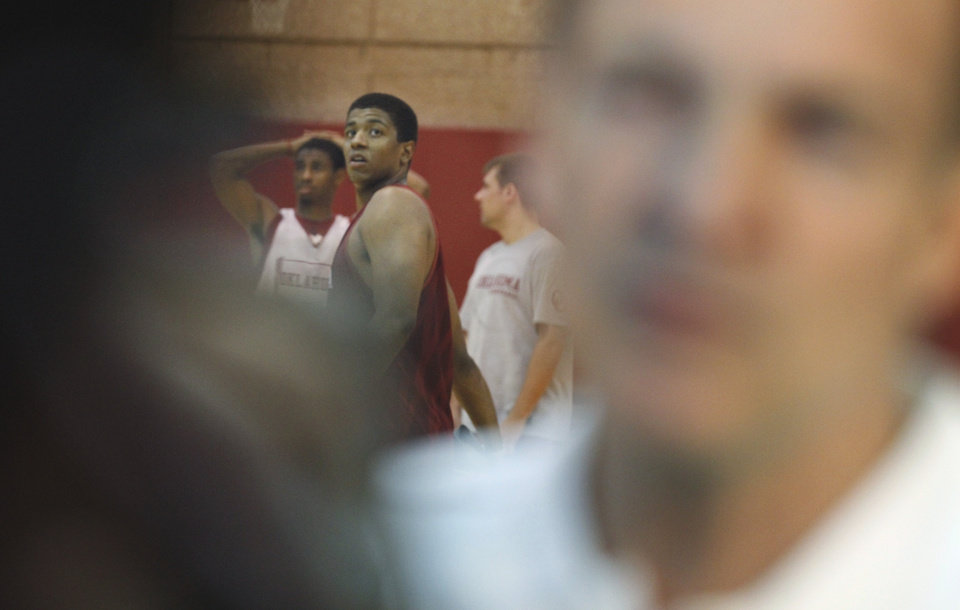 Players watch on the practice court as Lon Kruger, new University of Oklahoma (OU) Sooner men's basketball head coach, talks to the media after the team