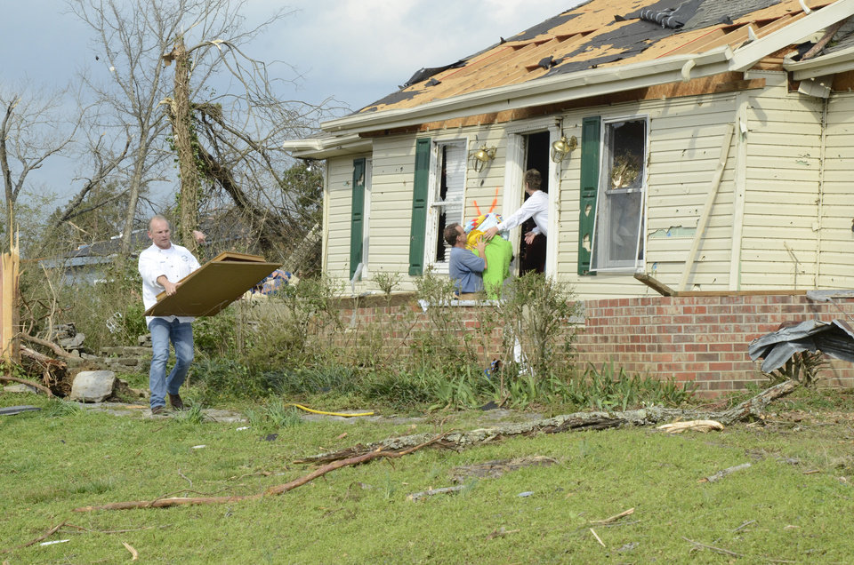 Stan Carnahan, left, carries items from his mother's Ooltewah-Georgetown Road home after a tornado hit Friday, March 2, 2012 in Ooltewah, Tenn.  Powerful storms stretching from the Gulf Coast to the Great Lakes flattened buildings in several states, wrecked two Indiana towns and bred anxiety across a wide swath of the country in the second powerful tornado outbreak this week.  (AP Photo/Chattanooga Times Free Press, Angela Lewis) MANDATORY CREDIT ORG XMIT: TNCHA110