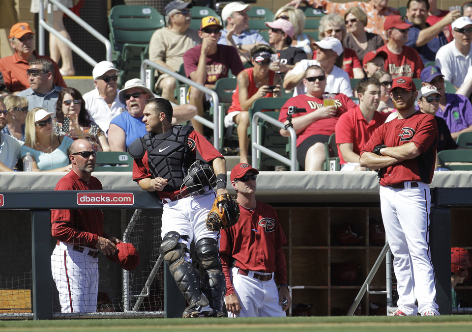 Photo -   Arizona Diamondbacks manager Kirk Gibson, from left, Miguel Monterom Charles Nagy and Ian Kennedy wait as the game is delayed because of a swarm of bees during the second inning of a spring training baseball game against the San Francisco Giants, Sunday, March 4, 2012, in Scottsdale, Ariz. (AP Photo/Darron Cummings)