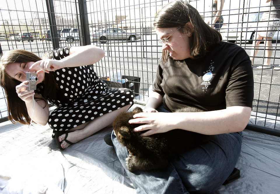 Amber Lowry of Edmond, Okla., takes pictures of her friend Stephanie Knoblock Cleveland, Ohio holding Edith, a 6-week-old North American black bear at Bryant Square Shopping Center in Edmond, Okla., on Saturday, April 5, 2008. The cub was part of G.W. Exotic Animal Park's road show. BY SARAH PHIPPS, THE OKLAHOMAN