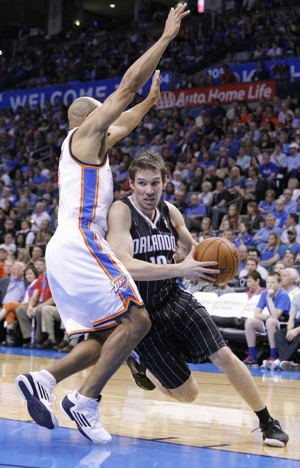 Photo - Orlando Magic guard Beno Udrih, right, drives to the basket around Oklahoma City Thunder's Derek Fisher, left, during the second quarter of an NBA basketball game in Oklahoma City, Friday, March 15, 2013. (AP Photo/Alonzo Adams)
