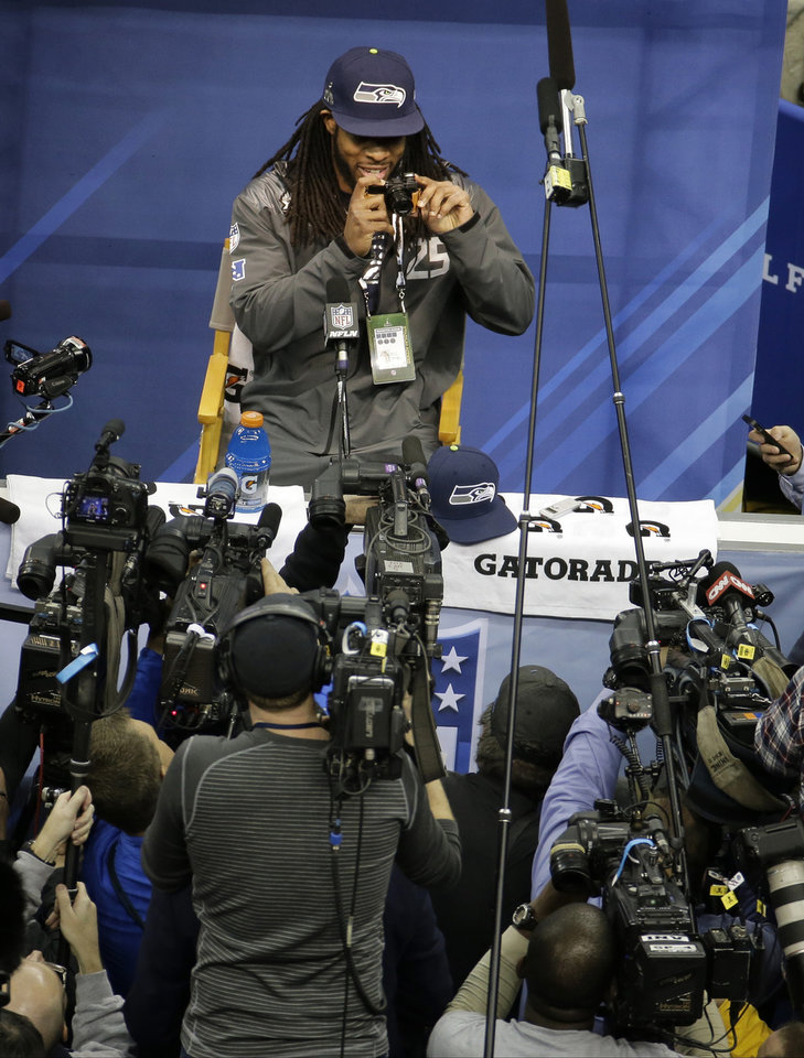 Photo - Seattle Seahawks' Richard Sherman takes pictures during media day for the NFL Super Bowl XLVIII football game Tuesday, Jan. 28, 2014, in Newark, N.J. (AP Photo/Charlie Riedel)